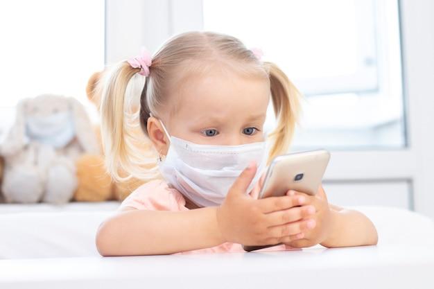 Девушка в защитной медицинской маске с помощью мобильного телефона.