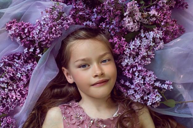 紫色の花のドレスの女の子はライラックの花の間にあります
