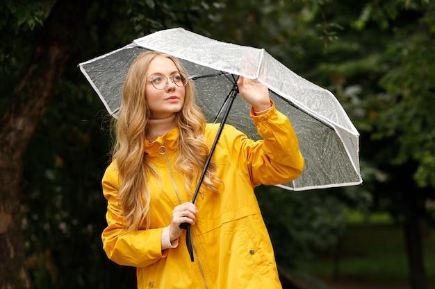 緑の背景に秋の傘とレインコートの女の子