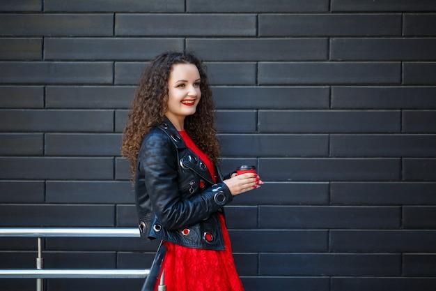 赤いドレスと黒いジャケットの女の子は赤い紙コップからコーヒーを飲みます