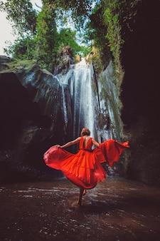 Девушка в красном платье танцует в водопаде.