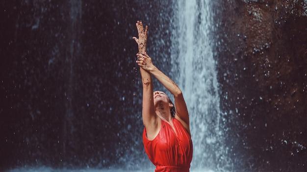 滝で踊る赤いドレスを着た女の子。