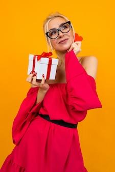 Девушка в красном платье держит подарок и красное сердце на оранжевом студийном фоне