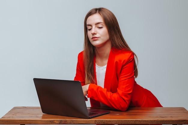 Девушка в красной куртке с ноутбуком за столом светлом фоне