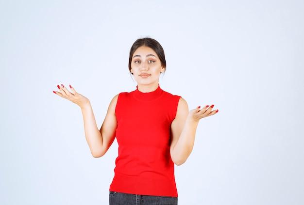 ポジティブで魅惑的なポーズをする赤いシャツを着た女の子。