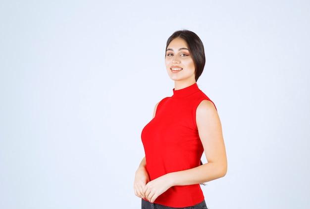 Девушка в красной рубашке дает положительные и соблазнительные позы.