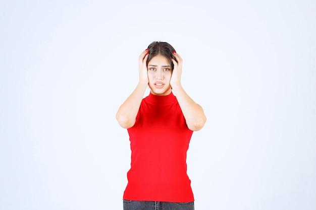 빨간 셔츠를 입은 소녀는 무서워하고 겁에 질려 보입니다.