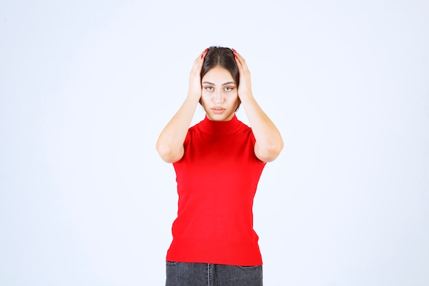 赤いシャツを着た女の子は、怖がって怯えているように見えます。