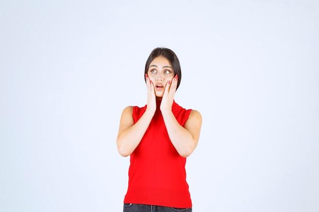 Девушка в красной рубашке выглядит напуганной и напуганной. Бесплатные Фотографии