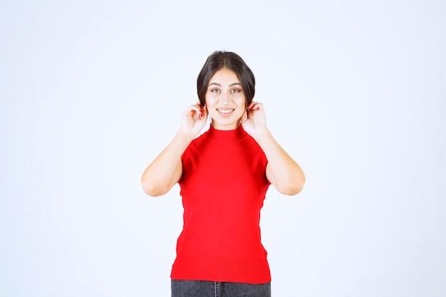 Девушка в красной рубашке дергает за уши в знак невезения.