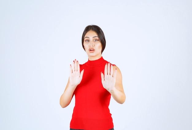 手で何かを止める赤いシャツの女の子。
