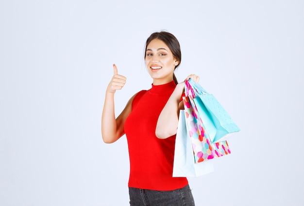 Девушка в красной рубашке с красочными сумками.