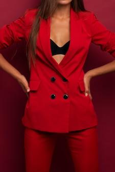胃を美しいプレスで赤いスーツの女の子。