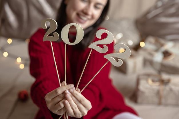 빨간 스웨터를 입은 소녀는 막대기에 나무 숫자 2022를 들고 보케가 있는 흐릿한 배경을 가지고 있습니다.