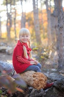 秋の森の赤いセーターの女の子。