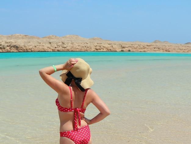 Девушка в красном купальнике и пляжной шляпе стоит лицом к солнцу в море. загорает стоя в голубой прозрачной воде.