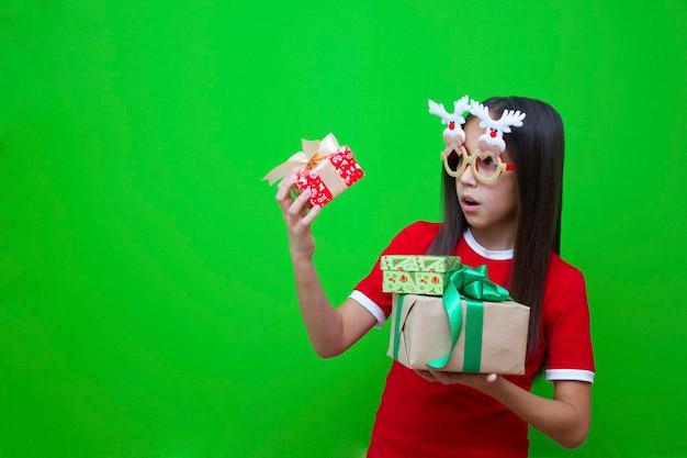 깜짝 놀란 빨간 티셔츠를 입은 소녀가 크리스마스 새해 선물이 든 상자를 들고 있다