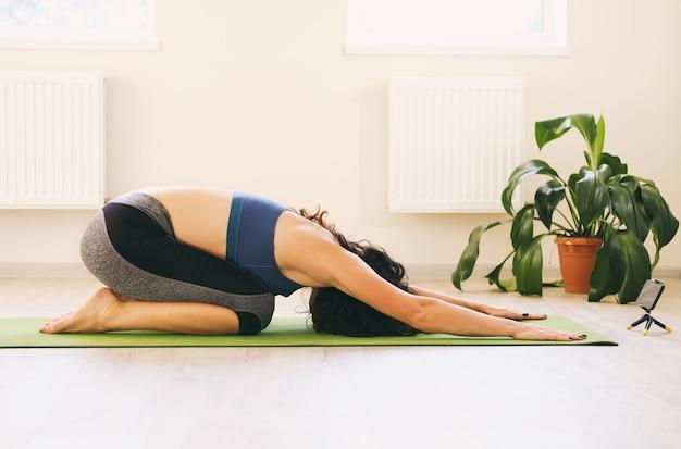 Девушка в расслабленном положении на полу дома - женщина делает тренировку дома