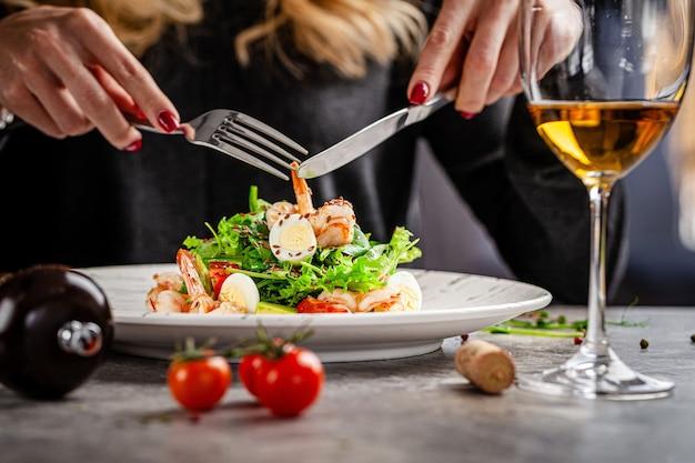 해산물과 새우와 시저 샐러드를 먹는 식당에서 소녀. 테이블에 화이트 와인 한 잔. 현대적인 레스토랑에서 제공됩니다. 배경 이미지. 공간 복사