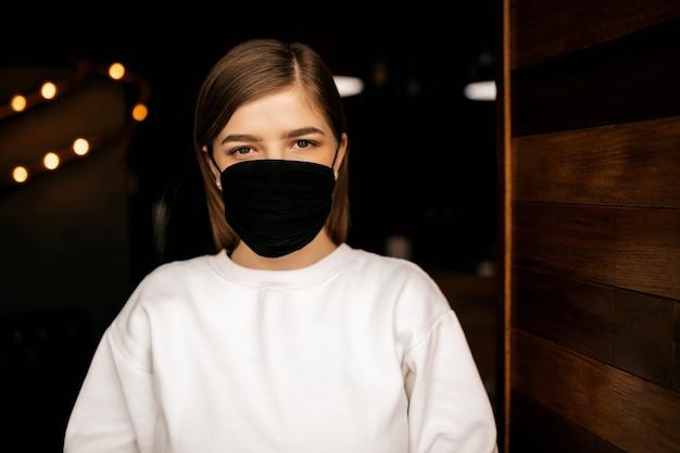 카메라, 어두운 배경에서 찾고 검은 의료 마스크에 레스토랑에서 소녀. 바이러스 보호.