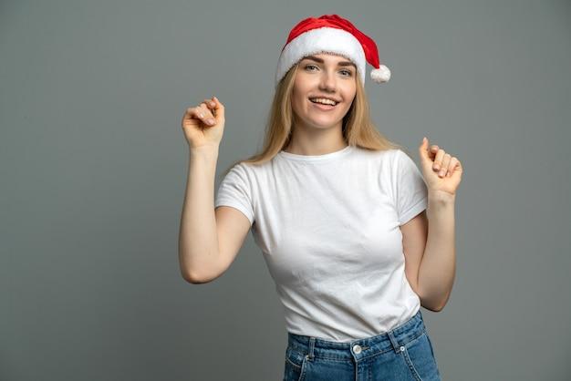 회색에 고립 된 산타 클로스 모자에 소녀