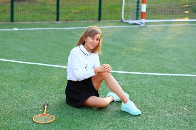 Девушка в школьной форме с ракеткой в руках на футбольном поле.