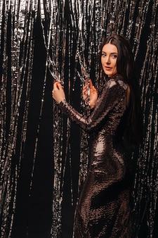 新年の雨の銀色の背景に光沢のあるドレスを着た女の子。