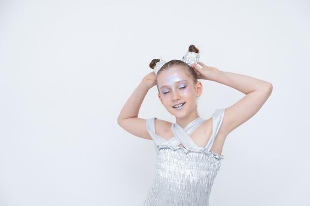 銀のドレスを着た女の子が目を閉じてポニーテールを保持