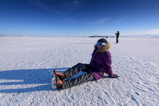 氷の上に座ってそれを結ぶ氷の上でスケートをするためのスケートの女の子、ロシア、バイカル湖