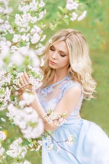 Девушка в весеннем саду вдыхает аромат цветущих деревьев