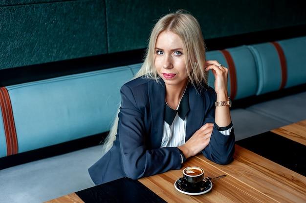 Девушка в строгом костюме в кафе пьет кофе