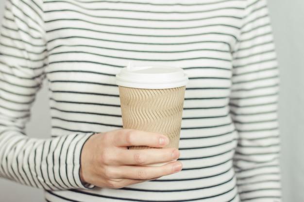 Девушка в полосатой футболке держит перед собой бумажный стаканчик с кофе или чаем.