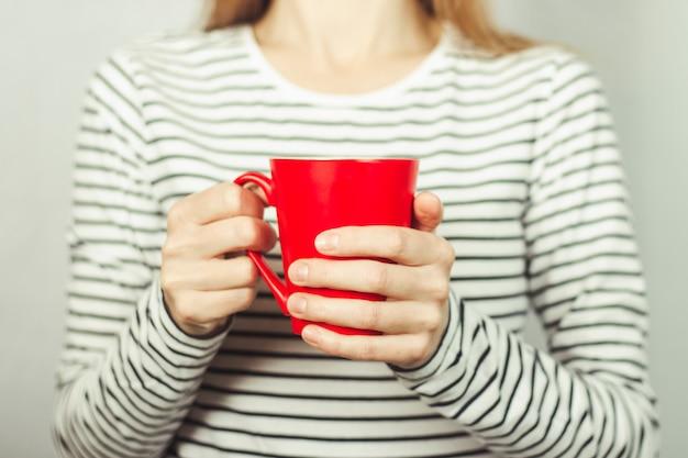 Девушка в полосатой футболке держит перед собой красную чашку кофе или чая. концепция завтрака, кофе-брейк.