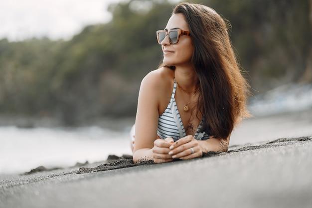 Девушка в стильном купальнике отдыхает на пляже