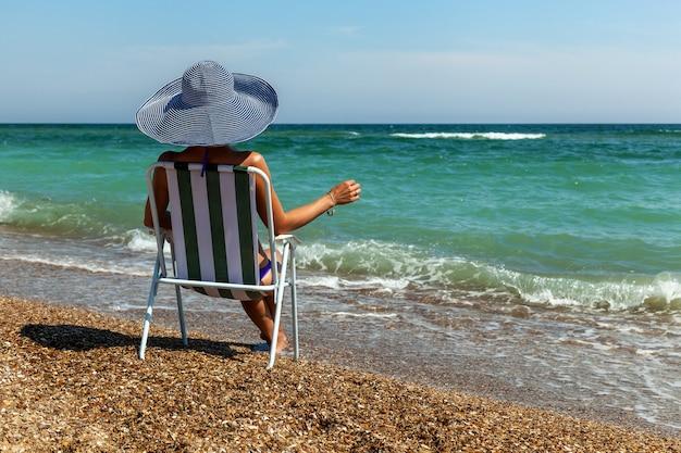 海の近くのサンラウンジャーの女の子は、風景を楽しんでいるように見えます