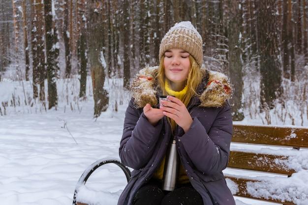 冬の公園でホットドリンクとカップ魔法瓶キャップを保持しているセーターの女の子