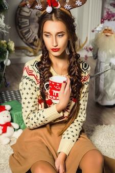 Девушка в свитере сидит в комнате с елочными украшениями