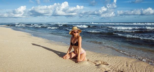 Девушка в купальнике и шляпе сидит на пляже баннерная панорама