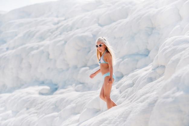 ホワイトマウンテン、晴れた日、パムッカレトルコの水着とサングラスの女の子。