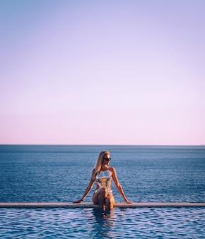 海を背景にパノラマプールの近くで水着を着た女の子がリラックス