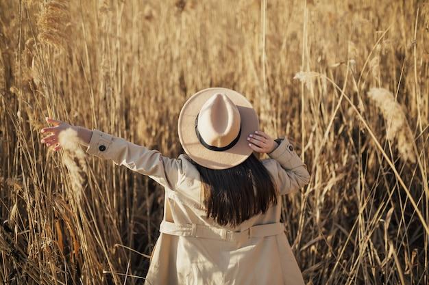乾いた葦を背景にトレンチコートと帽子の女の子