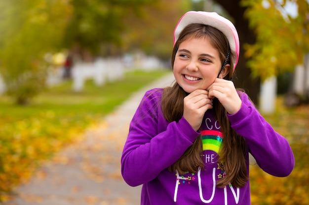 秋の公園で幸せな笑顔でトレンディなピンクのヘルメットの女の子。休暇の概念と時間を過ごす。