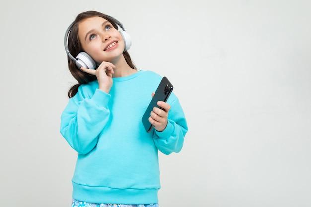 Девушка в бирюзовой блузке расслабляется с музыкой в наушниках