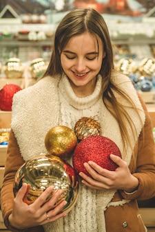Девушка в теплом пальто держит большой елочный шар