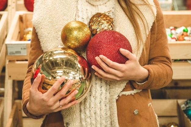 큰 크리스마스 공을 들고 따뜻한 코트에 소녀