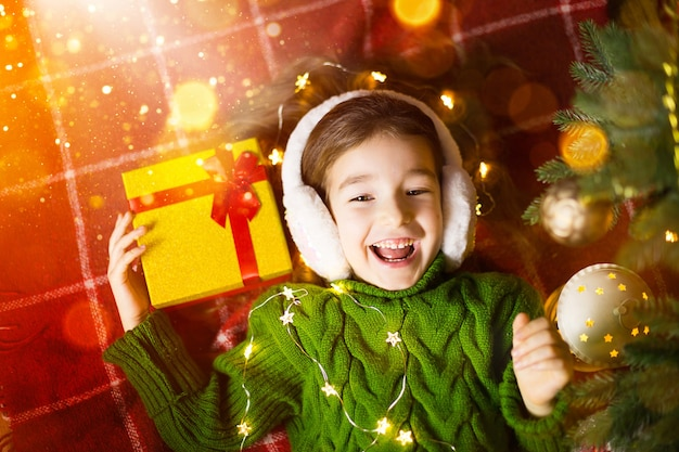 暖かいニットのセーターと毛皮のヘッドフォンを着た女の子が、クリスマスツリーの近くの毛布の上にギフトボックスを置いて横たわっています。クリスマスイブ、夢と願い。新年、お祭りの雰囲気、花輪とボケ