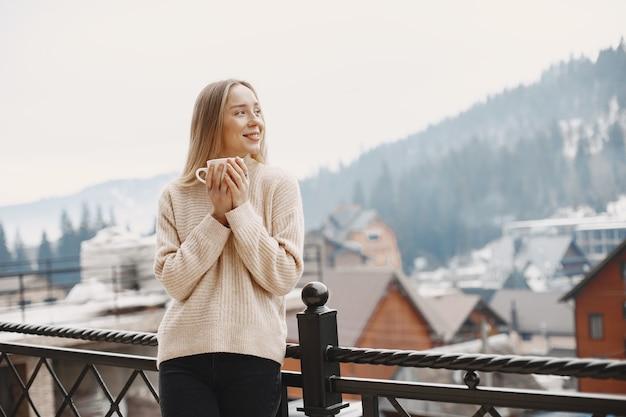 暖かい薄手のコートを着た女の子。山での休暇。長い髪の女性。