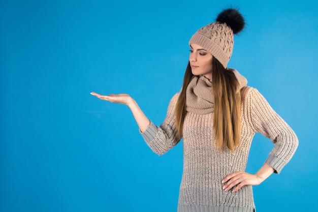Девушка в теплом свитере, шарфе и шляпе на синем фоне