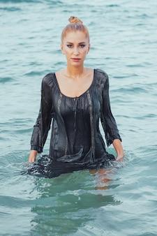 Девушка в мокром платье позирует в воде