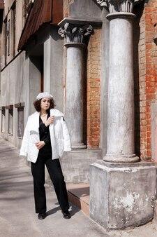 흰색 베레모와 오래 된 건물 근처 흰색 재킷에 소녀